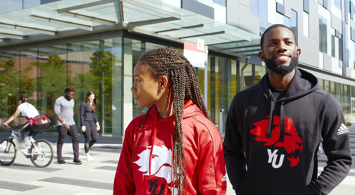 Two Black students standing prominently in front of Life Sciences Building, with students passing in the background